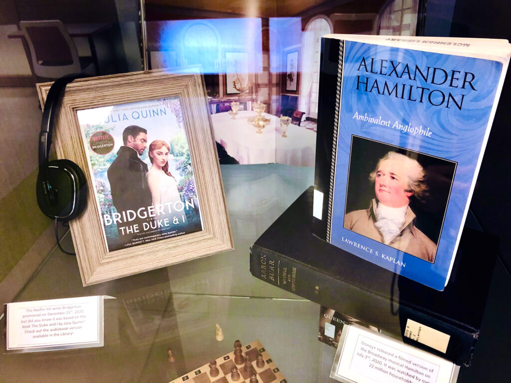 Books on Alexander Hamilton and Aaron Burr are tucked into the right hand side of the shelf. A framed photo of The Duke and I book cover sits on the shelf with a pair of headphones laid overtop to signify the audio version of the book.