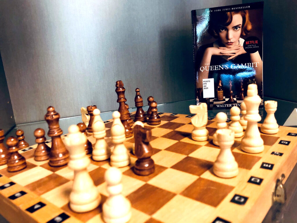 """A chess set is set up to depict a famous tournament match, behind it in the right top corner of the frame is the book """"The Queen's Gambit"""" by Walter Tevis."""