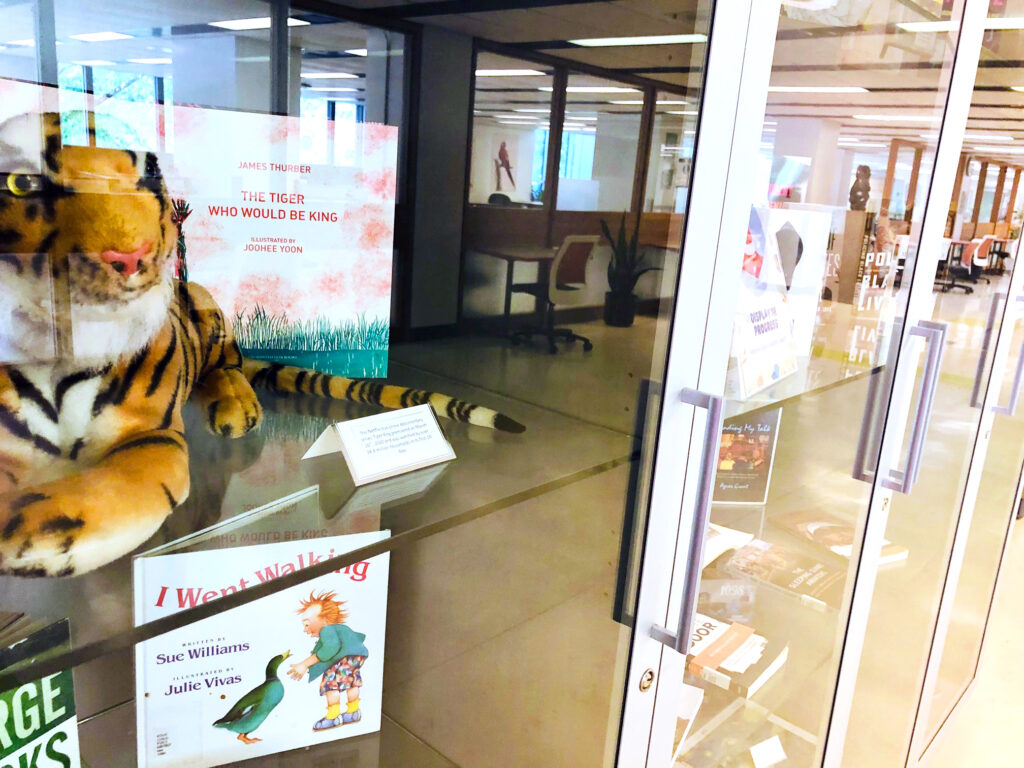 """side angle view of a stuff tiger and the book """"The Tiger Who Would Be King"""", a children's picture book flipped open to the first title page."""