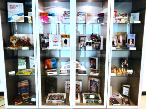 front angle view of the glass exhibition case featuring all sixteen shelves of material.