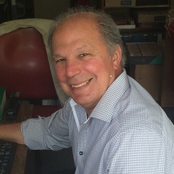 A man with short gray hair is smiling up at the camera from his desk. His right arm is outstretched toward the keybaord and behind him are lots of old books.