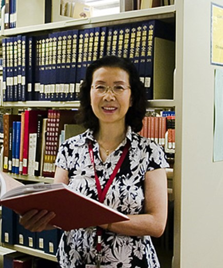 A woman with shoulder length black hair smiles at the camera while holding a large book open. She has frameless glasses and is wearing a lanyard. Behind her is a bookshelf.