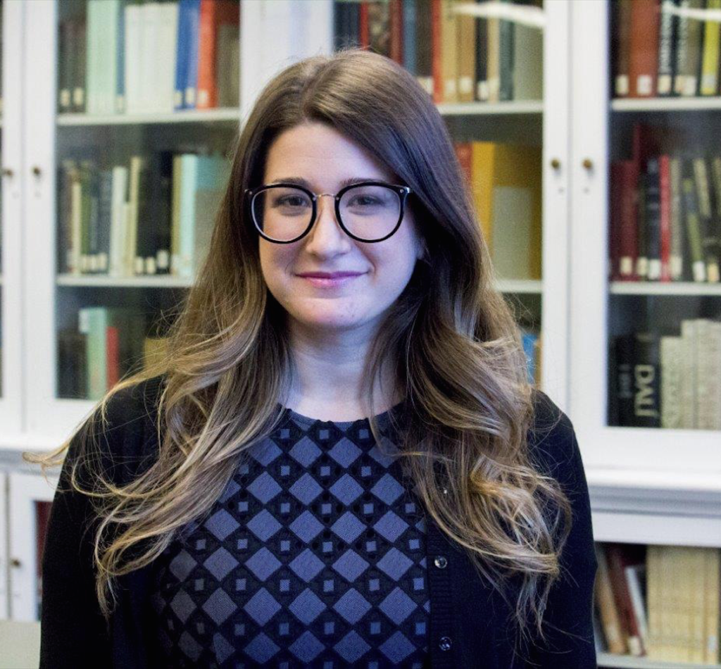 A young woman with long, wavy brown hair is smiling with closed lips at the camera. She has large black glasses and can be seen from the chest up. She is standing in front of a bookshelf.