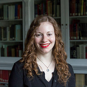 A young woman with curly red hair is smiling at the camera. She has on bright red lipstick and can be seen from the chest up. She is standing in front of a bookshelf.