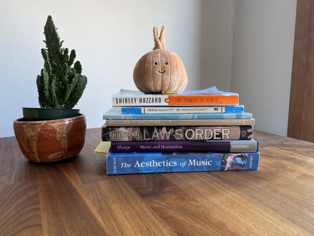 pile of books next to cactus